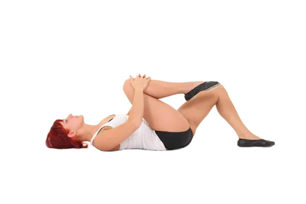 Woman stretching and warming up prior to exercise to prevent knee injury.